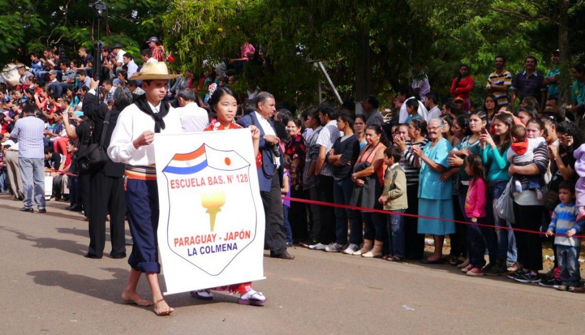 独立記念日パレード PARAGUAY-JAPON LA COLMENA のバナーを持って歩く子ども達