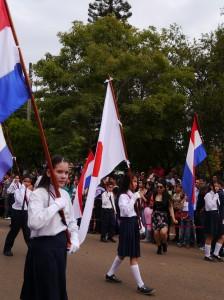 独立記念日パレード パラグアイと日本の国旗を持って歩く子ども達